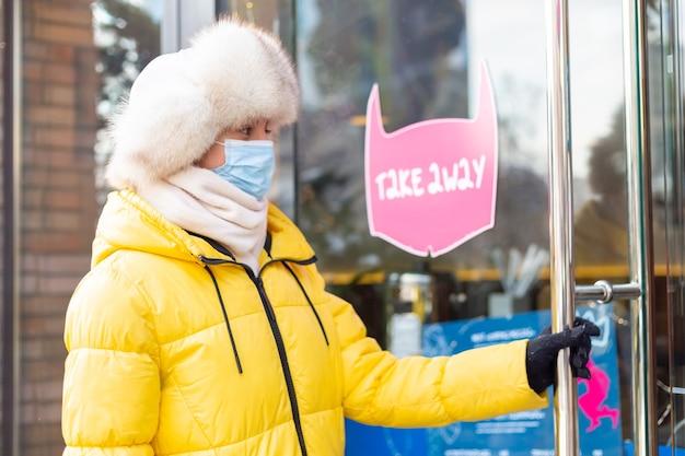 Счастливая молодая женщина у двери ресторана в холодный зимний день, надписи, еда на вынос.