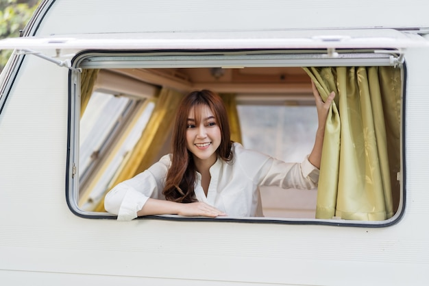 Счастливая молодая женщина у окна автодома автофургона фургон