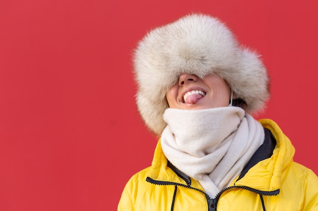 Happy young woman on the background of a red wall in warm clothes on a winter sunny day smiles with a snow-white smile