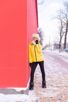 Felice giovane donna su uno sfondo di un muro rosso in vestiti caldi in una giornata di sole invernale sorridente e parlando al telefono su un marciapiede innevato della città