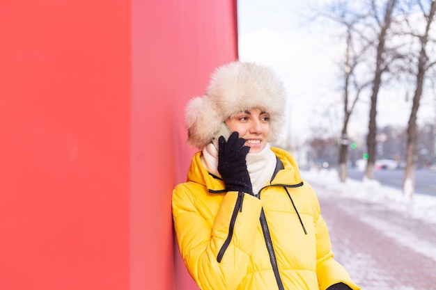 Happy young woman on a background of a red wall in warm clothes on a winter sunny day smiling and talking on the phone on a snowy city sidewalk