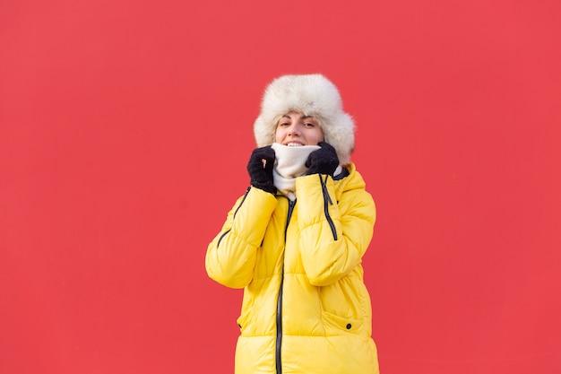 Felice giovane donna sullo sfondo di un muro rosso in vestiti caldi in una giornata di sole invernale