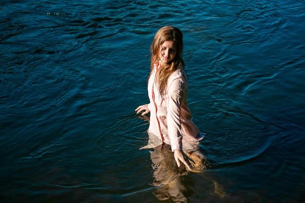 시원한 물을 즐기며 강에서 목욕하는 행복한 젊은 여성