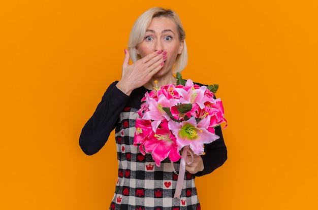 Giovane donna felice in vestito bello che tiene il mazzo di fiori che guarda l'obbiettivo