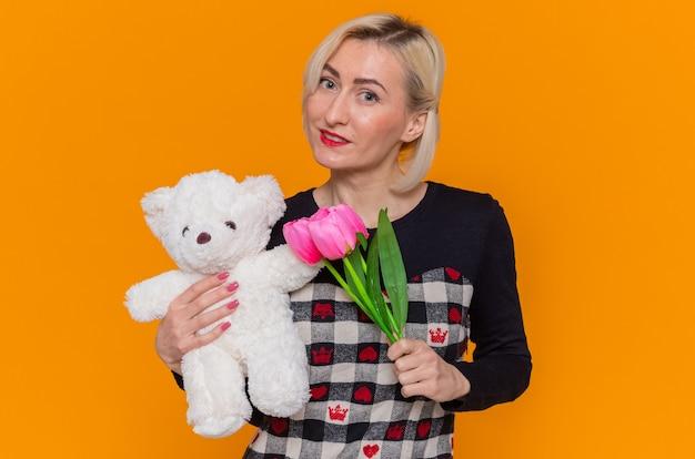 Giovane donna felice in vestito bello che tiene mazzo di tulipani e orsacchiotto come doni guardando davanti sorridente che celebra la giornata internazionale della donna in piedi sopra la parete arancione