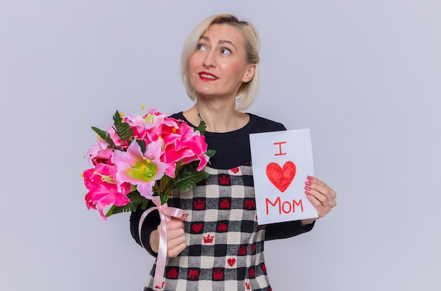 Happy young woman in beautiful dress holding greeting card and bouquet of flowers looking up smiling cheerfully celebrating mother's day standing over white wall