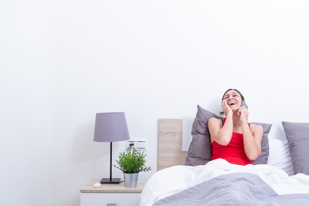Happy young woman in bed laughing out loud while talking on the mobile phone