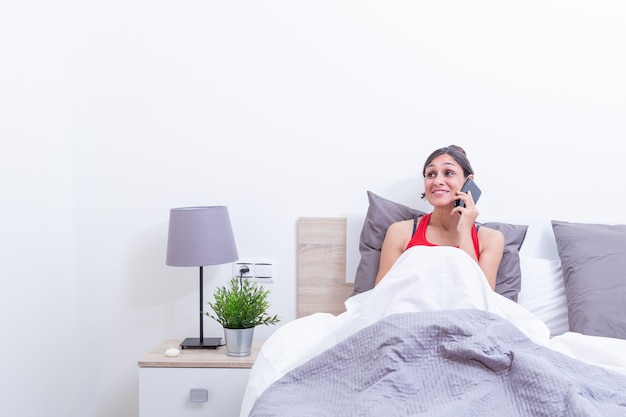 Happy young woman in bed smiling while listening on mobile phone