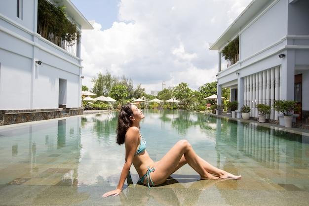 Happy young woman in bikini relaxing at poolside