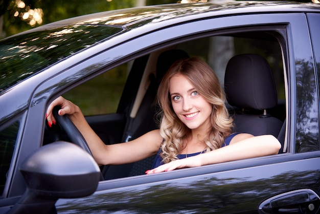 Happy young woman in a black auto.