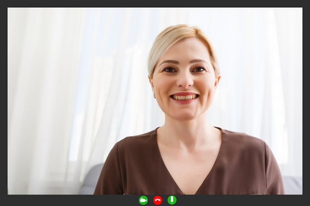 Happy young woman blogger applicant teacher sit at home office look at camera doing online job interview during video chat conference call record vlog teaching on webinar in app, webcam view