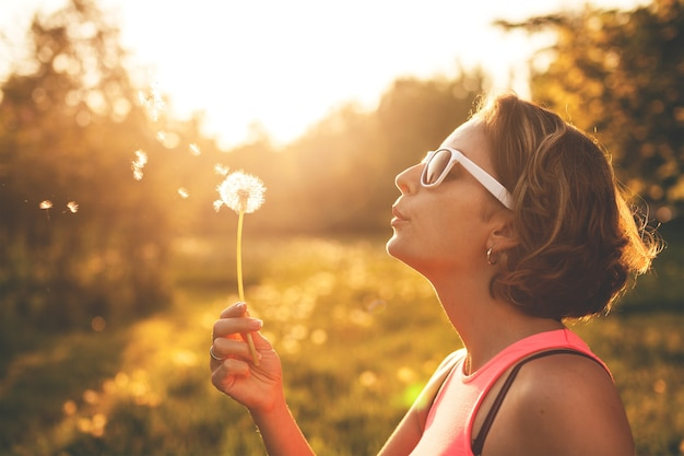 Happy young woman blowing on a dandelion in park