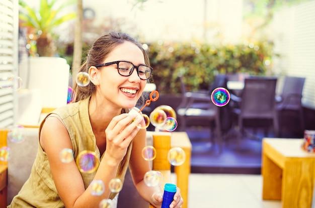 幸せな若い女がバーのレストランでシャボン玉を吹く