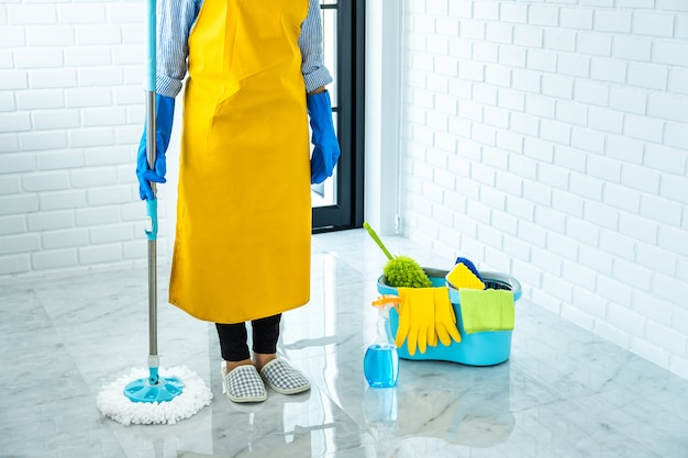 Happy young woman in blue rubber using mop while cleaning on floor at home