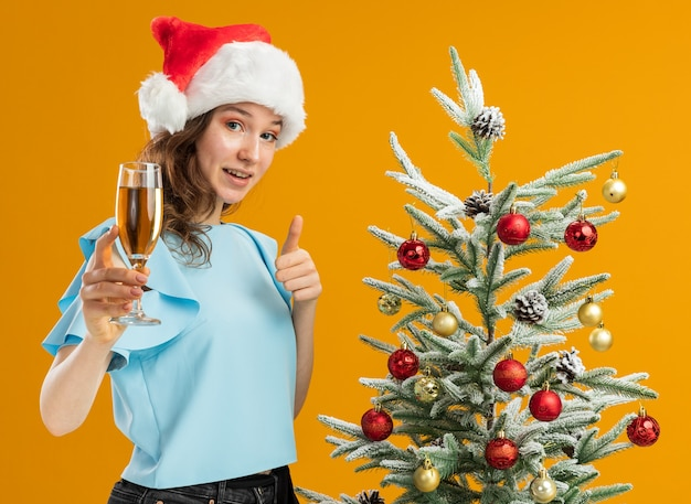 Happy young woman in blue top and santa hat  holding glass of champagne smiling showing  thumbs up standing next to a christmas tree over orange background