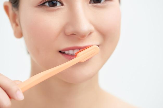 Счастливая молодая женщина, чистящая зубы щеткой.