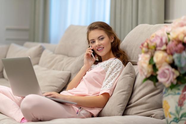 コンピューターで作業中のスマートフォンで呼び出す幸せな若い女性。携帯電話とラップトップを持つ魅力的な女性。