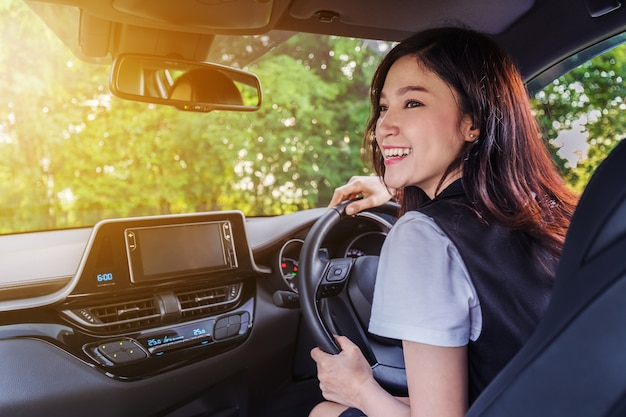 Happy young woman in car