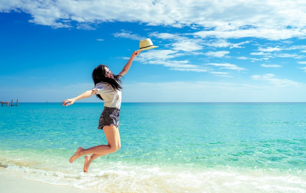 Happy young woman in casual style fashion and straw hat jumping at sand beach. relaxing and enjoy holiday at tropical paradise beach. girl in summer vacation. summer vibes.