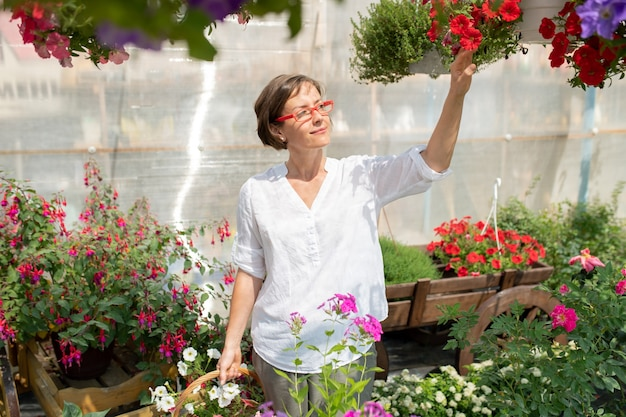 Happy young woman in casualwear touching one of potted petunias while standing among flowers