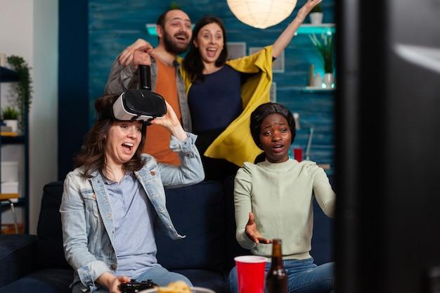 Счастливая молодая женщина празднует победу, играя в видеоигры с гарнитурой виртуальной реальности, и ее многонациональные друзья подбадривают ее, общаясь по вечерам.