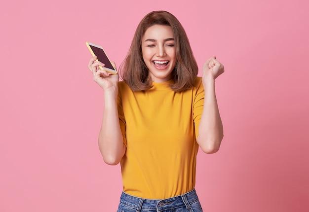 ピンクの背景で隔離の携帯電話で祝う幸せな若い女性。