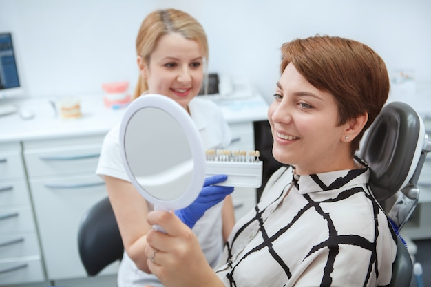 Happy young woman checking teeth in the mirror after teeth whitening