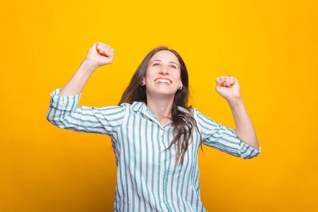 Счастливая молодая женщина, поднимая вверх обеими руками
