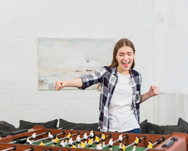 Счастливая молодая женщина, аплодисменты во время игры в настольный футбол дома