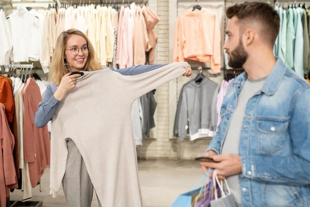 自分でドレスを選んで、モールで買い物中に彼氏に見せてくれる幸せな若い女性