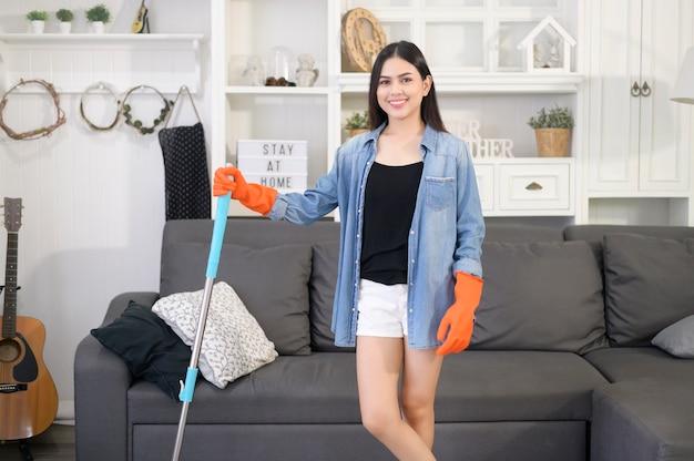 リビングルームでモップで床を掃除して幸せな若い女