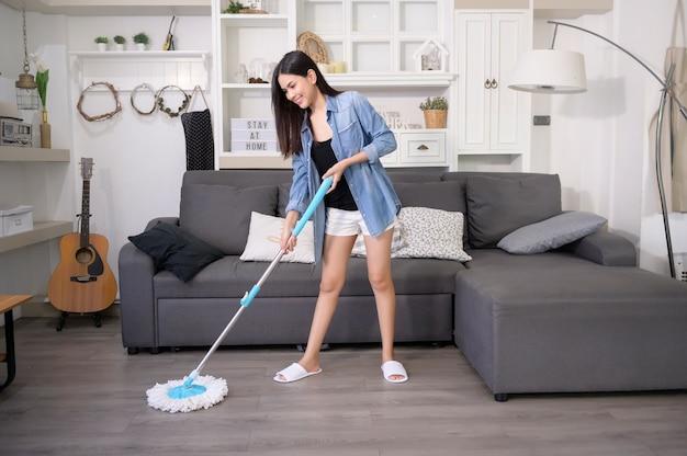 Счастливая молодая женщина, уборка пола шваброй в гостиной