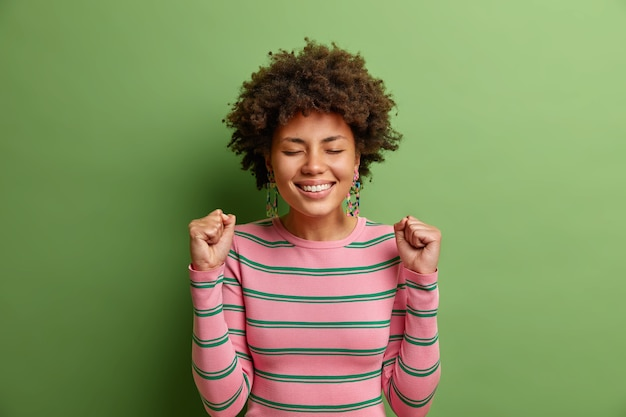 Happy young woman clenches fists celebrates success closes eyes and smiles broadly awaits for anouncement of results dressed in striped sweater isolated over vivid green wall