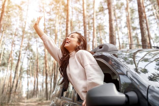 Счастливая молодая женщина вылезла из окна машины. путешествие на машине по лесу. загородная поездка отдых на машине