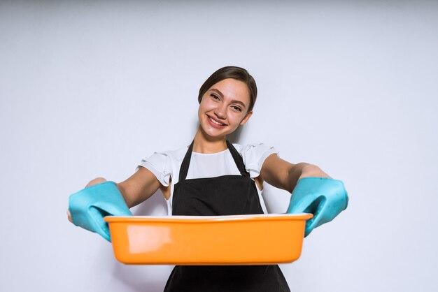 幸せな若い女性はオーブンで調理された、おいしいパイを焼いた黒いエプロンで調理します