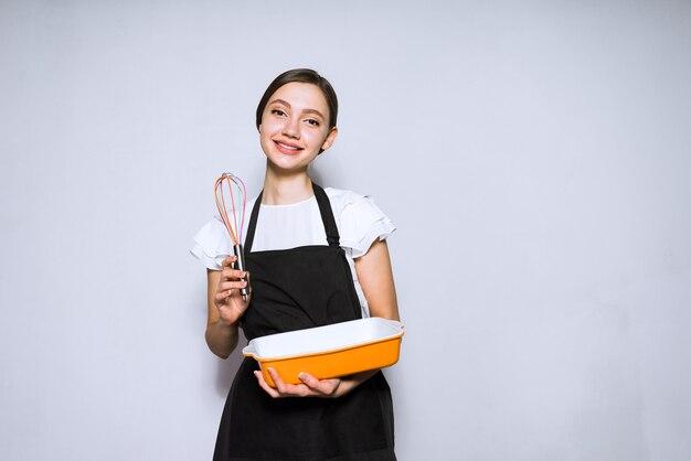 幸せな若い女性は夕食のためにおいしいパイを準備する黒いエプロンで調理します