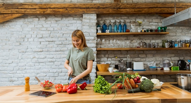 Happy young woman cooking delicious and healthy food in the loft kitchen at home