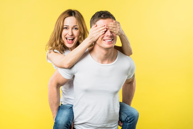 Happy young woman covering eyes while riding boyfriend's back against yellow backdrop
