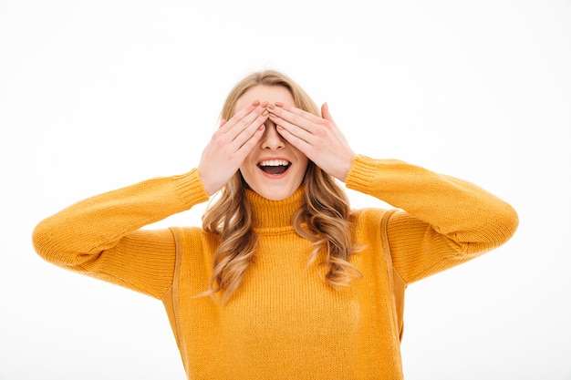 Happy young woman covering eyes with hands.