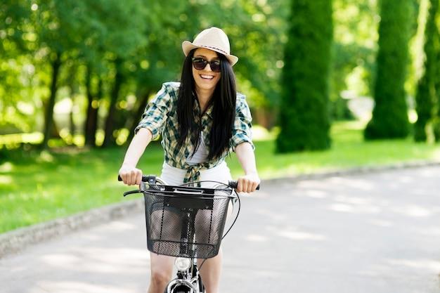 Felice giovane donna in bicicletta attraverso il parco