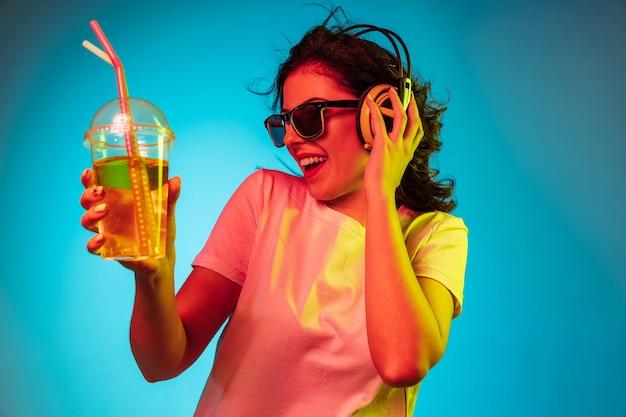 トレンディな青いネオンの上でヘッドフォンで踊って笑って幸せな若い女性