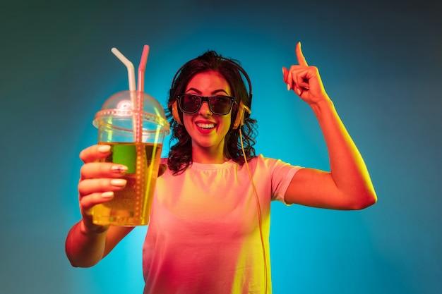 Giovane donna felice che balla e che sorride in cuffie sopra lo studio al neon blu alla moda