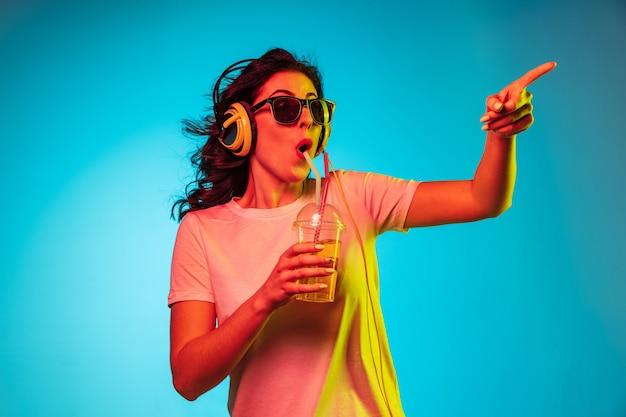 Felice giovane donna ballando e sorridendo in cuffia su neon blu alla moda