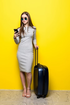 Happy young woman in dark glasses, carrying a suitcase and passport with tickets, uses a mobile phone on a yellow wall