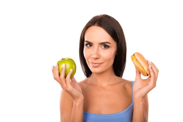 Счастливая молодая женщина, выбирая между яблоком и гамбургером