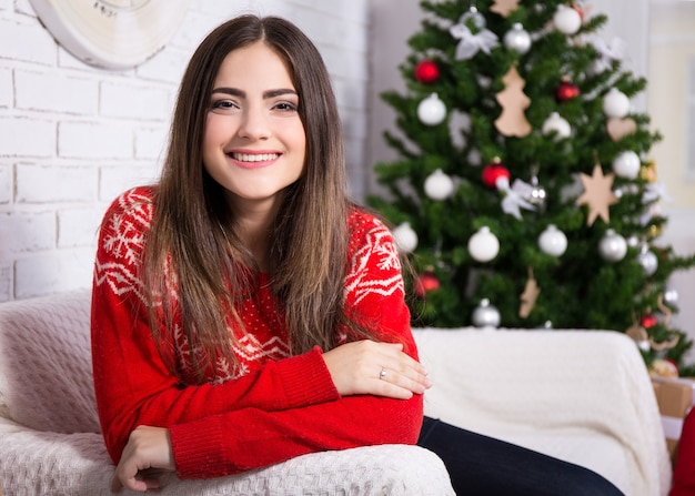 Happy young woman in decorated living room with christmas tree