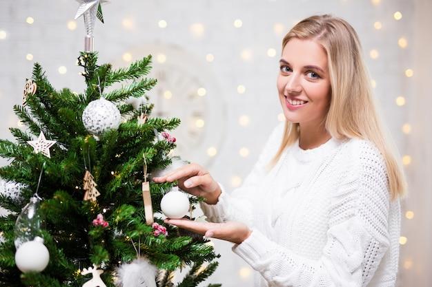 リビングルームでクリスマスツリーを飾る幸せな若い女性