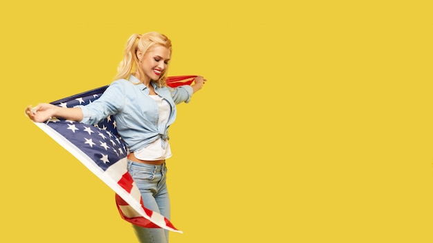 Happy young woman in denim clothes holding usa flag on yellow background.