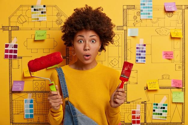 Progettista felice della giovane donna che pianifica il rinnovamento dell'appartamento moderno