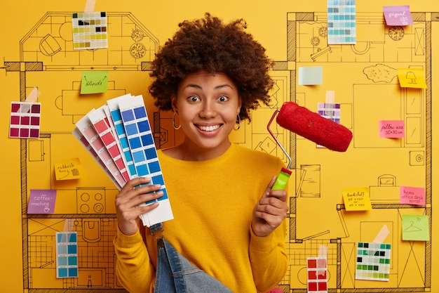 Happy young woman designer planning renovation of modern apartment